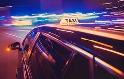 Taxi die een linkerdraai nemen bij nacht royalty-vrije stock afbeelding