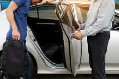 Taxi driver greeting his passengers with their luggage on the si. Dewalk of a modern city Stock Photos
