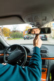 Taxi driver is looking in the driving mirror. Experienced taxi driver is looking in the rear view mirror in his taxi, he sets the taximeter Stock Photos