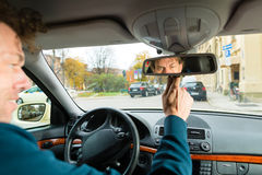 Taxi driver is looking in the driving mirror. Experienced taxi driver is looking in the rear view mirror in his taxi, he sets the taximeter Royalty Free Stock Image