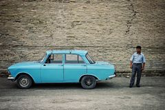 Taxi driver next to his classic soviet car in the historical walled city of the silk road stock photos