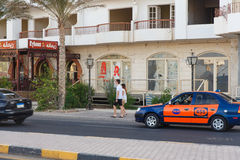 Taxi driver obsession offers its service. HURGHADA, EGYPT - MAY 20: Taxi driver obsession offers its service to a pair of European tourists. Hurghada, Egypt. May royalty free stock images