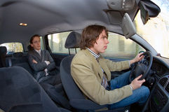Taxi driver and passenger. A businessman in the backseat of a taxi, driving through an urban area Stock Image