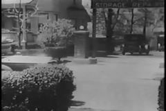 Taxi driver pulling up in front of house and taking hatbox out of car, 1930s stock footage