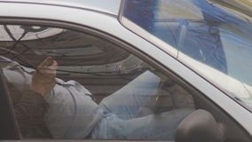 Taxi driver resting in his parked car while checking his mobile phone in hand. Most orders are received from the dispatcher. Through applications or calls in stock footage