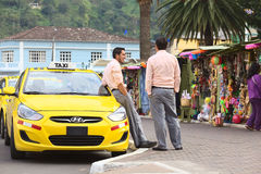 Taxi Drivers in Banos, Ecuador. BANOS, ECUADOR - FEBRUARY 22, 2014: Unidentified taxi drivers talking at taxi stand on 12 de Noviembre Street outside the Stock Photo