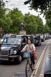 Taxi drivers on strike. LONDON, UK - JUNE 11, 2014: A cyclist passes a line of stationary taxis near Whitehall during a taxi driver strike Stock Image