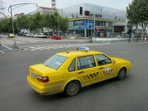 Taxi Driving Across Intersection. A yellow taxi drives across an intersection, transporting people to their destination royalty free stock photos