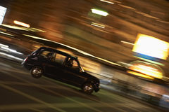 Taxi Driving Through Night Time Street Stock Image
