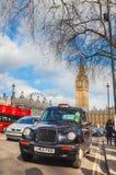 Taxi famoso en el cuadrado del parlamento en Londres Fotografía de archivo