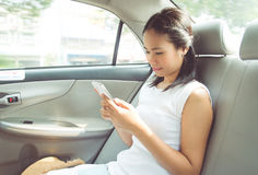 Taxi fare. Thai woman in the taxi with smart phone royalty free stock photography
