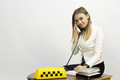 Taxi - girl dispatcher and other materials on the topic of taxi. Taxi industry - dispatcher work reception of orders waiting for the car, telephone conversations stock photography