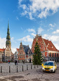 Taxi at House of Blackheads and Christmas tree in Riga. Riga, Latvia - December 26, 2015: Taxi car and People at the House of the Blackheads and the Christmas royalty free stock photos