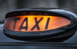 Taxi. Illuminated black cab taxi sign Stock Image