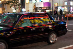 A taxi in Japan. A taxi going by, with neon signs reflected in its windows stock photography