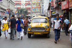 Taxi in Kolkata, India. Urban scene in Kolkata, India. A local taxi driver is driving among the people along the street around Hogg Market. The metered-cabs are Royalty Free Stock Image