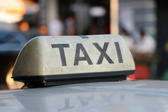 Taxi light sign or cab sign in drab white color and black text on the car roof. At the street blurred background, Myanmar royalty free stock photo