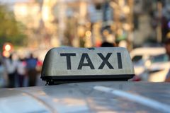 Taxi light sign or cab sign in drab white color and black text on the car roof. At the street blurred background, Myanmar stock photography