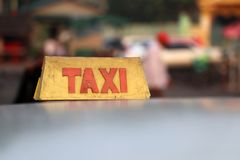 Taxi light sign or cab sign in drab yellow color with red text on the car roof. At the street blurred background, Myanmar stock photography