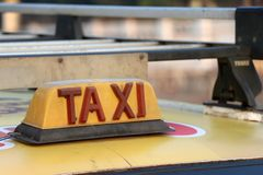 Taxi light sign or cab sign in drab yellow color with red text on the car roof. At the street blurred background, Myanmar royalty free stock images