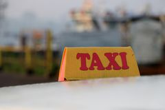 Taxi light sign or cab sign in drab yellow color with red text on the car roof. At the street blurred background, Myanmar royalty free stock photos