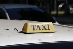 Taxi light sign or cab sign in drab brown color with black text on the car roof at the street blurred background. Myanmar stock photos