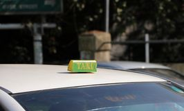 Taxi light sign or cab sign in drab green color with yellow text on the car roof at the street blurred background. Myanmar royalty free stock images
