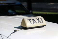 Taxi light sign or cab sign in drab white color with black text on the car roof at the street blurred background. Myanmar royalty free stock photos
