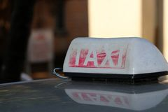 Taxi light sign or cab sign in drab white and fade away red color with white text on the car roof at the street. Blurred background, Myanmar royalty free stock images