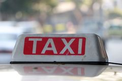 Taxi light sign or cab sign in drab white and red color with white text on the car roof at the street. Blurred background, Myanmar stock photography