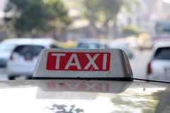 Taxi light sign or cab sign in drab white and red color with white text on the car roof at the street. Blurred background, Myanmar royalty free stock photography