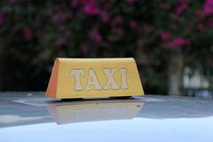 Taxi light sign or cab sign in drab yellow color with white text on the car roof at the street blurred background. Myanmar stock image