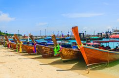 Taxi long-tail boats wait for tourists on beach, sunny day. Thailand Stock Images