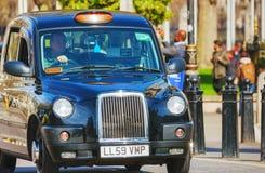 Taxi negro famoso una calle en Londres Imagenes de archivo