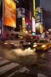 Taxi och bussar förbigår på fyrkanten för den upptagna gatan tidvis, Manhattan Arkivfoto