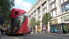 Taxi och den röda dubbla däckaren London bussar köra förgångna Selfridges, den Oxford gatan, London, England arkivfilmer