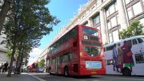 Taxi och den röda dubbla däckaren London bussar köra förgångna Selfridges, den Oxford gatan, London, England lager videofilmer