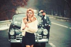 Taxi op weg met luxepaar taxibestuurder en vrouw bij retro auto stock afbeelding