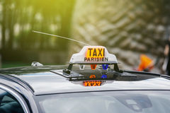 Taxi Parisien - Paris Taxi sign sunny day. Taxi Parisien - Paris Taxi sing on the roof of a transportation car in French Captial on a sunny day Stock Photo