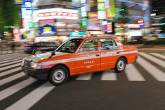 A taxi passes through Shinjuku Crossing in Tokyo, Japan. Shinjuku Tokyo is one of the busiest areas in the world Royalty Free Stock Photos