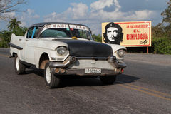 Taxi and a poster. VINALES, CUBA, FEBRUARY 20, 2014 : Old American car and a Che Guevara poster. Classic cars are still in use in Cuba and old timers have become royalty free stock photos