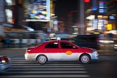 Taxi que acomete en la noche Imagen de archivo