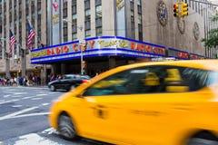 Taxi que conduce por de radio teatro de variedades la ciudad Foto de archivo libre de regalías