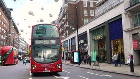 Taxi, röda London för dubbel däckare bussar och shoppareOxford gata, London, England arkivfilmer