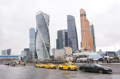 Taxi rank along the road near Moscow city in cloudy weather. Cars, buildings, skyscrapers stock photos