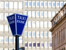 Taxi Rank Sign. A blue and white Taxi Rank sign in a city environment with tall buildings in the background royalty free stock photography