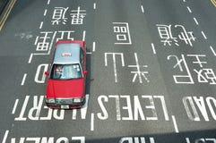 Taxi rojo que conduce en el distrito central de Hong Kong Island Fotografía de archivo
