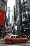 Taxi rojo que espera en un paso de peatones en Hong Kong Island en China imagen de archivo