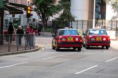 Taxi rojo y blanco de los colores, símbolo de HK, en el camino de Hollywood cerca del distrito pálido de la central y de Sheung;  imagenes de archivo