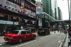 Taxi rojo y una precipitación en una calle de Hong Kong fotos de archivo